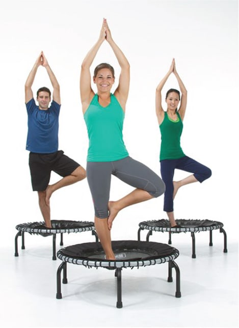 3 people, each standing in yoga pose, with hands over head and one leg making triangle with other leg, on their own JumpSport fitness trampoline