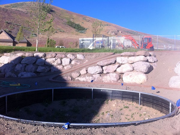 Retaining wall for an in-ground trampoline larger and with drainage